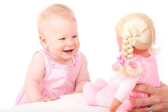 holčička smějící se na panenku